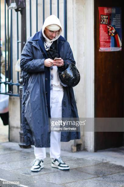 A guest wears a white hoodie sweater top a white beanie hat glasses white pants sneakers shoes and a long blue coat outside the JOUR/NE show during...