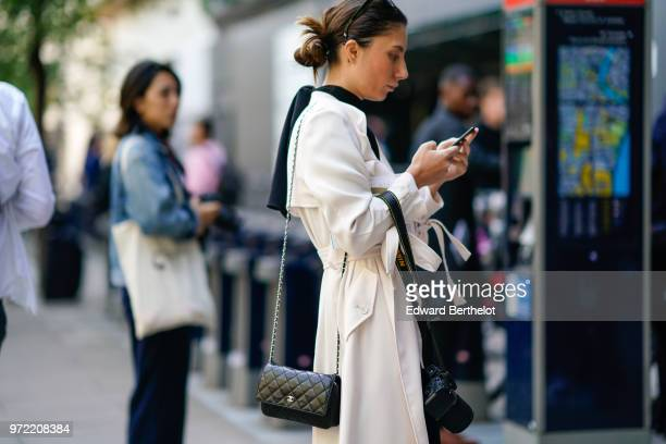A guest wears a white jacket a black Chanel bag holds a Nikon camera a mobile phone during London Fashion Week Men's June 2018 on June 09 2018 in...