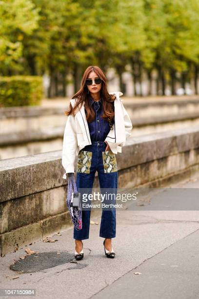 A guest wears a white jacket a blue denim outfit with snake print pockets shoes outside Valentino during Paris Fashion Week Womenswear Spring/Summer...