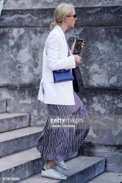 A guest wears a white jacket a bue bag a striped dress sneakers outside the Ralph Russo show during Paris Fashion Week Haute Couture Fall/Winter...