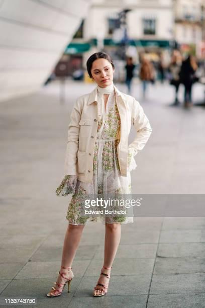 Guest wears a white jacket, a see-through white lace dress, sandals, outside Giambattista Valli, during Paris Fashion Week Womenswear Fall/Winter...