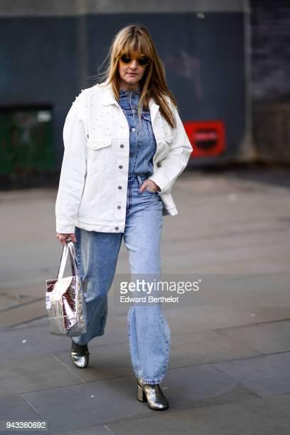 A guest wears a white jacket a silver bag a blue denim shirt blue denim pants silver shoes sunglasses during London Fashion Week February 2018 on...