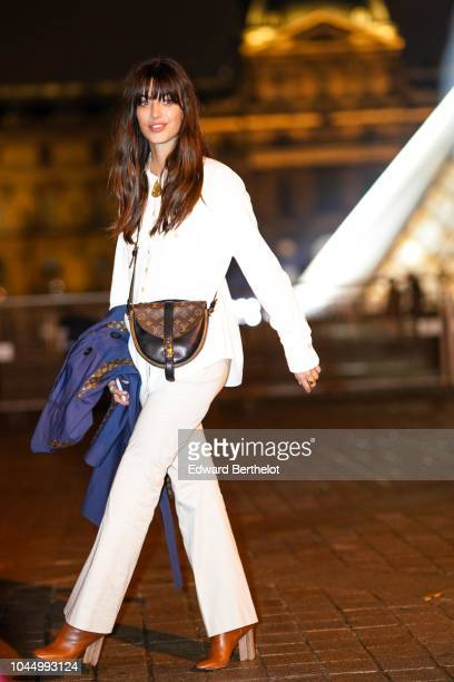 A guest wears a white jacket a Vuitton bag flare pants outside Vuitton during Paris Fashion Week Womenswear Spring/Summer 2019 on October 2 2018 in...