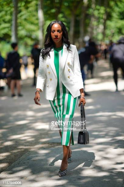 A guest wears a white jacket a white dress with green large stripes a bracelet a black Chanel bag black and white zebra pattern mules outside Berluti...