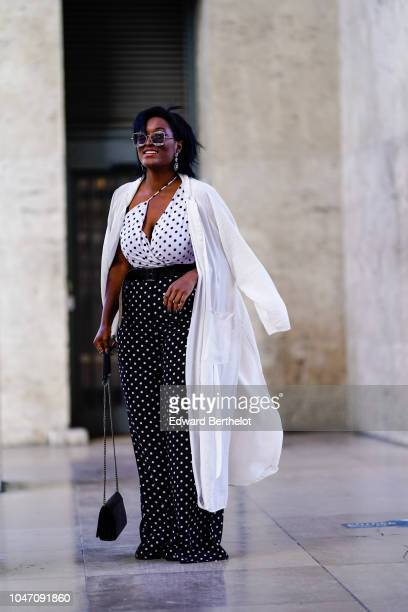 A guest wears a white jacket a white low neck top with printed polka dots black flared pants with printed white polka dots outside Shiatzy Chen...