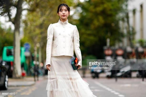A guest wears a white jacket a white mesh lace pleated skirt shoes a clutch outside Shiatzy Chen during Paris Fashion Week Womenswear Spring/Summer...