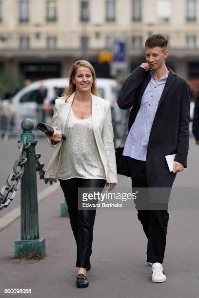 A guest wears a white jacket a white shiny top black shiny pants a black bag black moccasins a guest wears a blue shirt a dark grey coat black pants...