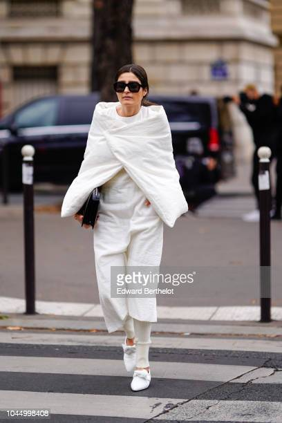 A guest wears a white jacket a white skirt white shoes white pants sunglasses outside Miu Miu during Paris Fashion Week Womenswear Spring/Summer 2019...