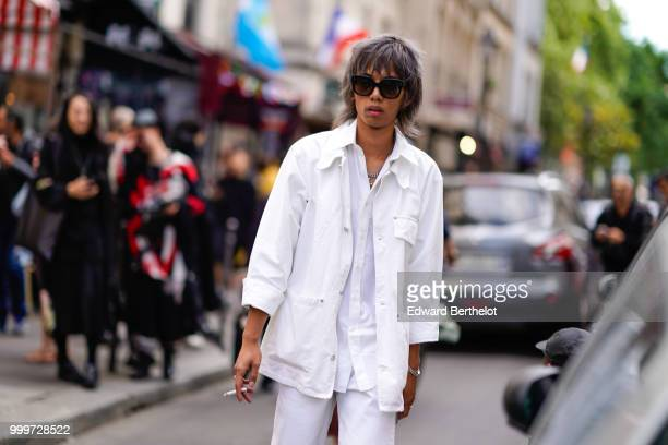 A guest wears a white jacket and a white shirt outside Yohji Yamamoto during Paris Fashion Week Menswear SpringSummer 2019 on June 21 2018 in Paris...