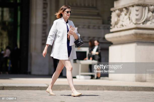 A guest wears a white jacket flat shoes outside the Chanel show during Paris Fashion Week Haute Couture Fall/Winter 20172018 on July 4 2017 in Paris...