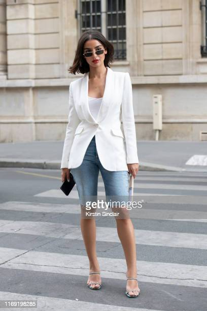 A guest wears a white jacket white vest top blue knee length denim shorts silver framed sunglasses and diamante heeled sandals on July 01 2019 in...