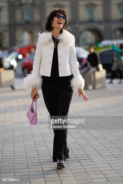 A guest wears a white jacket with fur black flare pants a pink bag outside Louis Vuitton during Paris Fashion Week Womenswear Spring/Summer 2018 on...