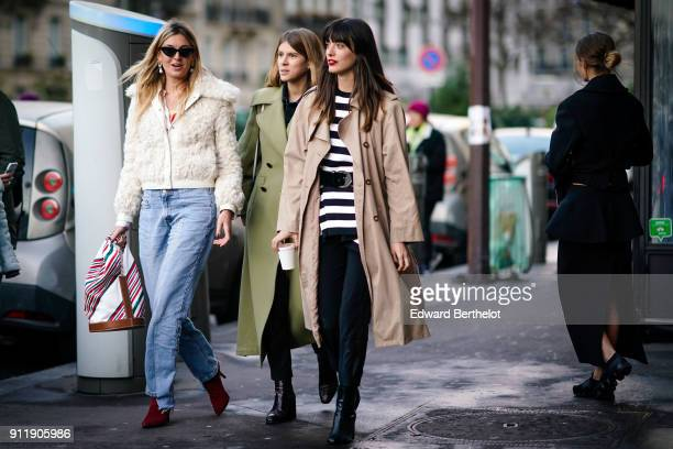A guest wears a white jacket with fur blue jeans a guest wears a green trench coat a guest wears a trench coat and a black and white striped dress a...