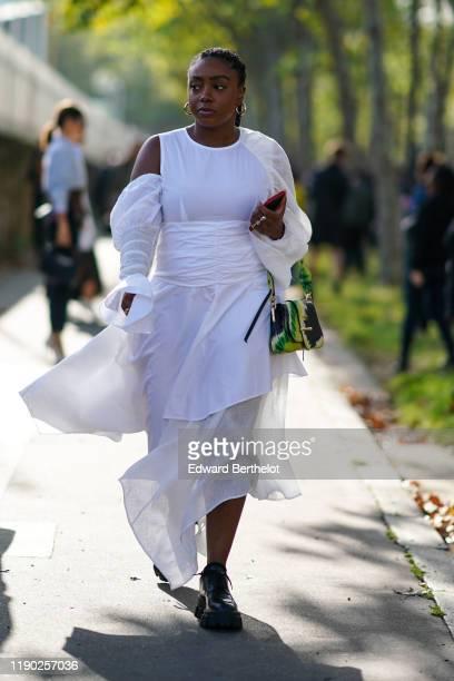 Guest wears a white lac emesh dress, a green bag, black leather shoes, earrings, outside Loewe, during Paris Fashion Week - Womenswear Spring Summer...