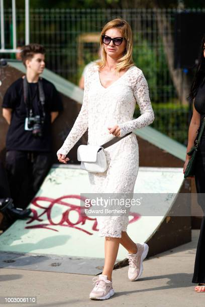 A guest wears a white lace dress a white belt bag sneakers during Feeric Fashion Week 2018 on July 20 2018 in Sibiu Romania