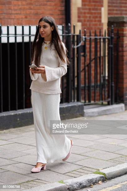 A guest wears a white lace dress a white pull over outside JW Anderson during London Fashion Week September 2017 on September 16 2017 in London...