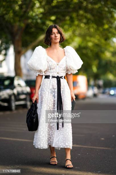 A guest wears a white lace dress with embroidery and puffed shoulders a black bag sandals earrings during London Fashion Week September 2019 on...