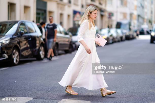 A guest wears a white lace dress with golden shoes outside Acne Studios during Paris Fashion Week Womenswear Fall Winter 2019 on July 1 2018 in Paris...