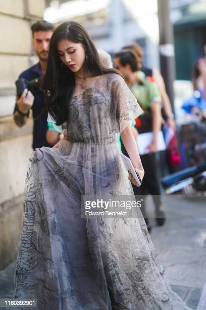 A guest wears a white lace dress with printed features outside Valentino during Paris Fashion Week Haute Couture Fall/Winter 2019/2020 on July 03...