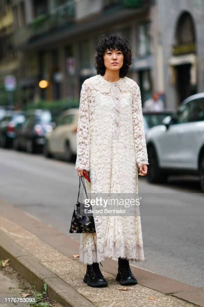 A guest wears a white lace long dress a black brocade bag black militarystyle boots outside the Dolce Gabbana show during Milan Fashion Week...