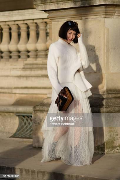 A guest wears a white lace mesh dress a Vuitton rectangular bag outside Louis Vuitton during Paris Fashion Week Womenswear Spring/Summer 2018 on...