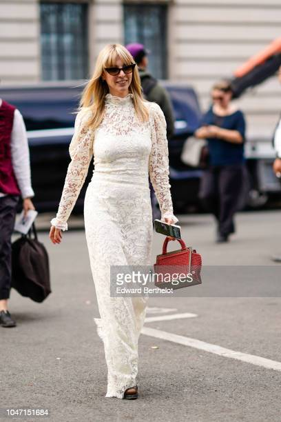 A guest wears a white lace mesh dress and a red bag outside Akris during Paris Fashion Week Womenswear Spring/Summer 2019 on September 30 2018 in...
