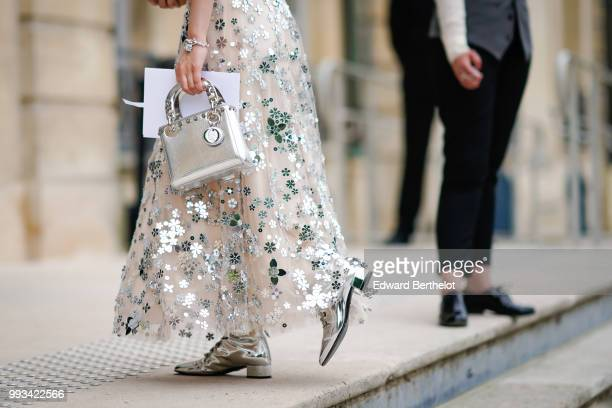 A guest wears a white lace mesh dress with embroidered shiny silver flowers a silver Lady Dior bag outside Dior during Paris Fashion Week Haute...