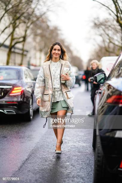 A guest wears a white lace mesh top a green skirt shoes a sleeveless jacket outside Valentino during Paris Fashion Week Womenswear Fall/Winter...