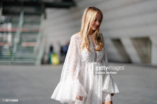 Guest wears a white lace see-through dress, outside Giambattista Valli, during Paris Fashion Week Womenswear Fall/Winter 2019/2020, on March 04, 2019...