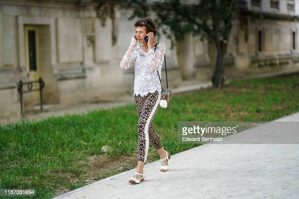 Guest wears a white lace top, leopard print crop pants with a white stripe on the side, white sandals, a leopard pattern bag, outside AMI, during...