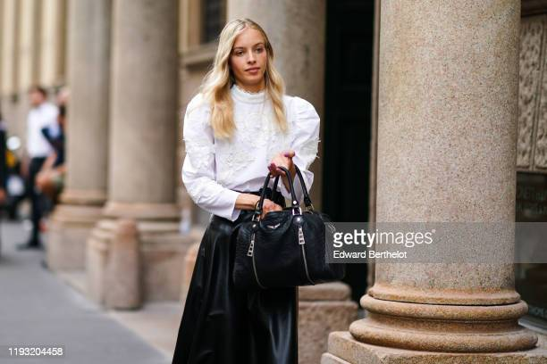 Guest wears a white lace Victorian -style blouse, a black leather skirt, a black elephant skin pattern handbag, outside the Peter Pilotto show during...