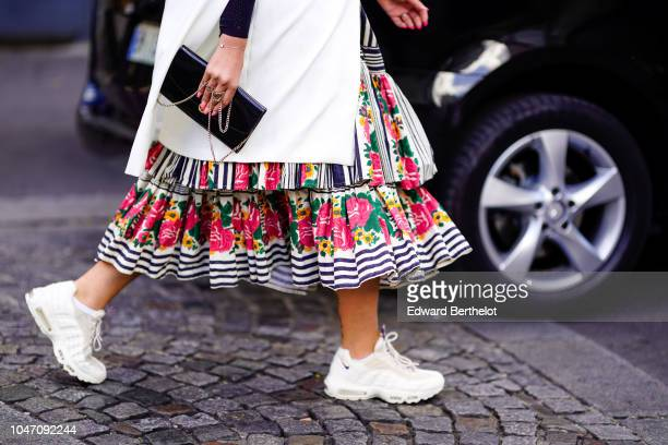 A guest wears a white long jacket a colored floral print ruffled pleated dress white sneakers shoes outside APC during Paris Fashion Week Womenswear...