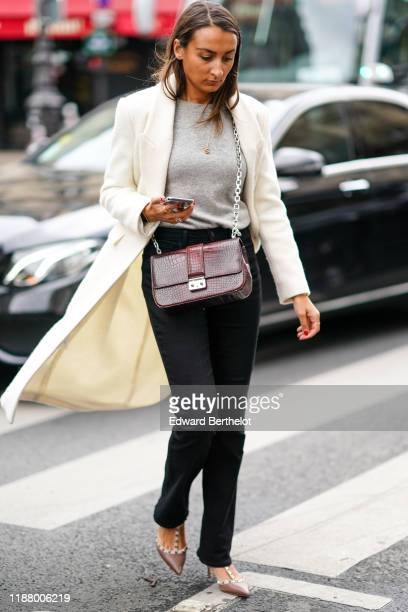 Guest wears a white long jacket, a gray pullover, a burgundy crocodile pattern bag, black pants, studded pointy shoes, outside Ralph & Russo, during...