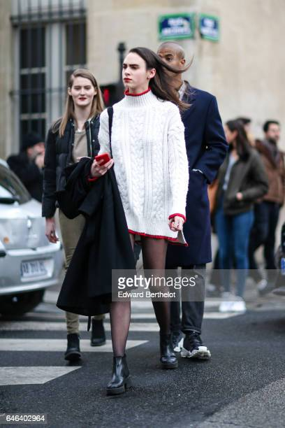 A guest wears a white long wool pull over as a dress with red edges black tights and black boots outside the JOUR/NE show during Paris Fashion Week...