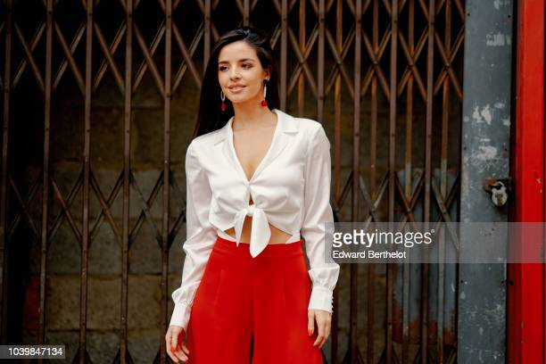 A guest wears a white low neck shirt red flared pants during London Fashion Week September 2018 on September 18 2018 in London England