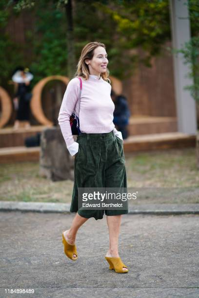 Guest wears a white mandarin-collar shirt, a colorful velvet bag, a light pink knit sweater, a forest-green suede divided skirt, mustard-color suede...