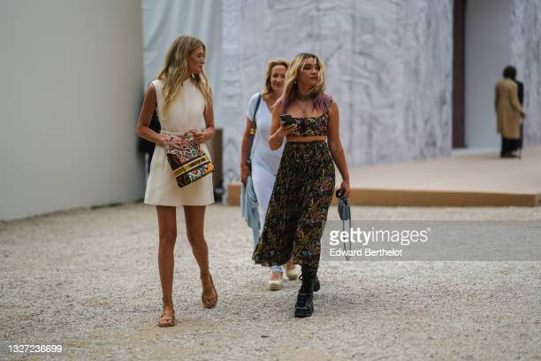 Guest wears a white matte sleeveless leather belted short dress from Dior, a white leather with green / red / orange / yellow embroidered pattern...