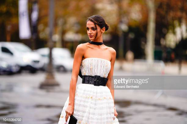 A guest wears a white offshoulder pleated lace mesh dress outside Chanel during Paris Fashion Week Womenswear Spring/Summer 2019 on October 2 2018 in...