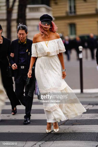 A guest wears a white offshoulder ruffle dress outside Miu Miu during Paris Fashion Week Womenswear Spring/Summer 2019 on October 2 2018 in Paris...