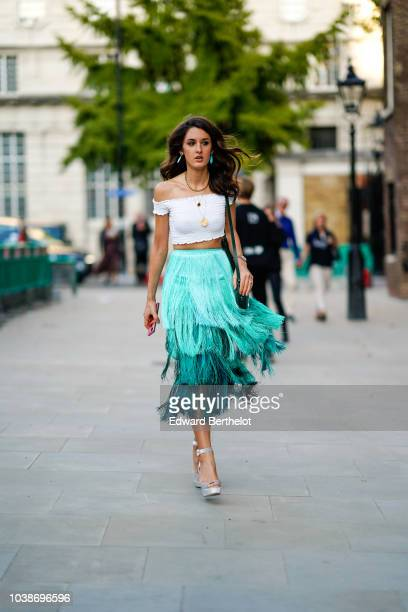 A guest wears a white offshoulder top a blue fringed skirt during London Fashion Week September 2018 on September 16 2018 in London England