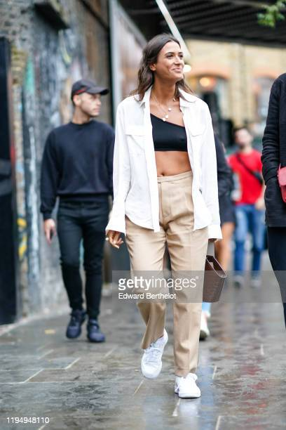 A guest wears a white open shirt black bras beige pants white sneakers shoes a necklace a crocodile pattern leather bag during London Fashion Week...