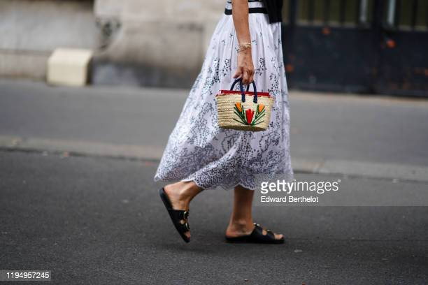 A guest wears a white openwork broderie anglaise pleated dress a small woven straw basket with colorful floral embroideries black flat sandals...