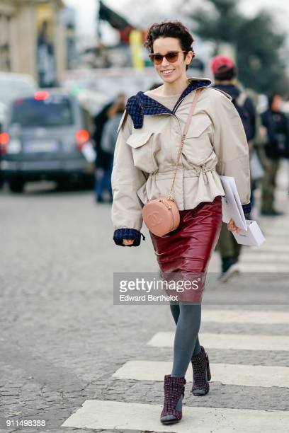 A guest wears a white oversize jacket a red plastic shiny skirt gray tights shoes a Chanel pink round bag sunglasses outside Chanel during Paris...