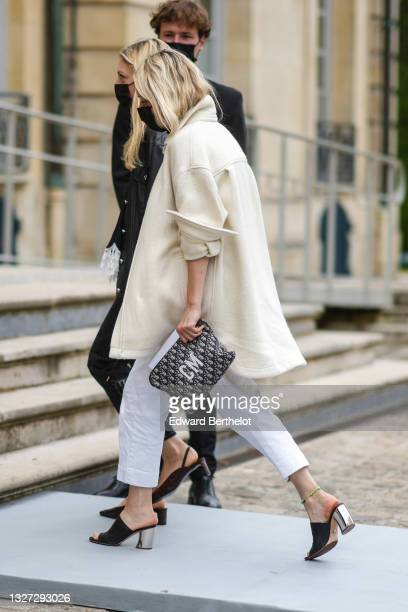 Guest wears a white oversized long coat, white denim jeans pants, a silver ring, blue and beige Dior Oblique Jacquard clutch from Dior with white CM...