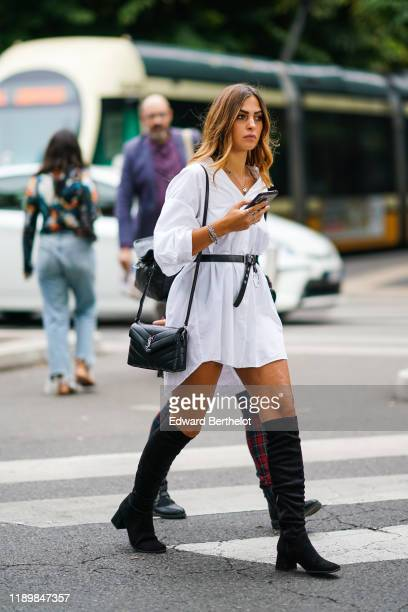 Guest wears a white oversized shirt, a black belt, a necklace, rings, a black Yves Saint Laurent bag, black suede knee-high boots, outside the Fendi...