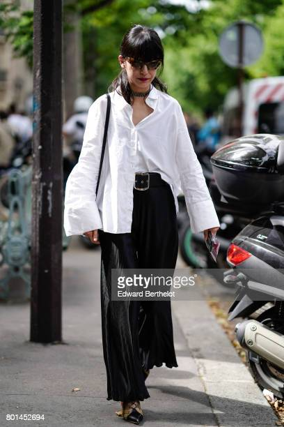 A guest wears a white oversized shirt black flared pants outside the Paul Smith show during Paris Fashion Week Menswear Spring/Summer 2018 on June 25...