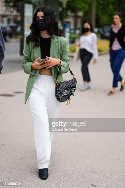 Guest wears a white pearls and red cherry pendant necklace and matching bracelet, a black crop-top, a green blazer jacket, white suit pants, gold...