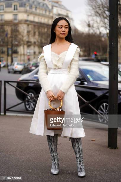 Guest wears a white pleated dress, an off-shoulder wool pullover, a brown leather bag with wooden handle, pointy boots, outside Miu Miu, during Paris...