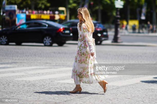 A guest wears a white pleated dress with floral print outside Chanel during Paris Fashion Week Haute Couture Fall/Winter 2019/2020 on July 02 2019 in...