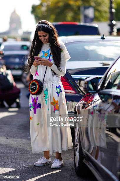 A guest wears a white pleated dress with printed colored stars a round bag white sneakers uses a smartphone to send text messages outside Elie Saab...